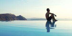 Man Sits Reflecting on Edge of Infinity Pool